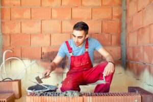portrait of mason working and building brick walls. Industrial, professional constructor renovating